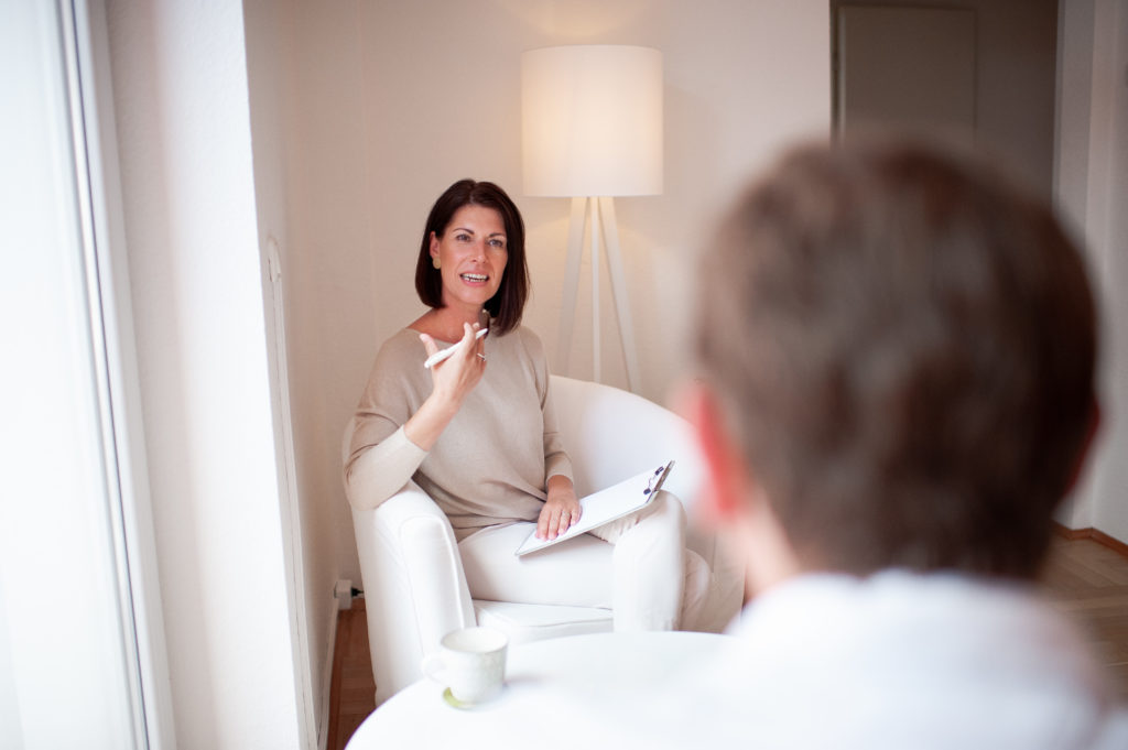 Andrea Lawlor gestikuliert mit ihrer Hand um eine These im Coaching-Gespräch zu unterstreichen.