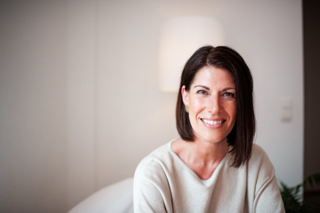 Andrea Lawlor sitzt auf Stuhl und hört aufmerksam zu