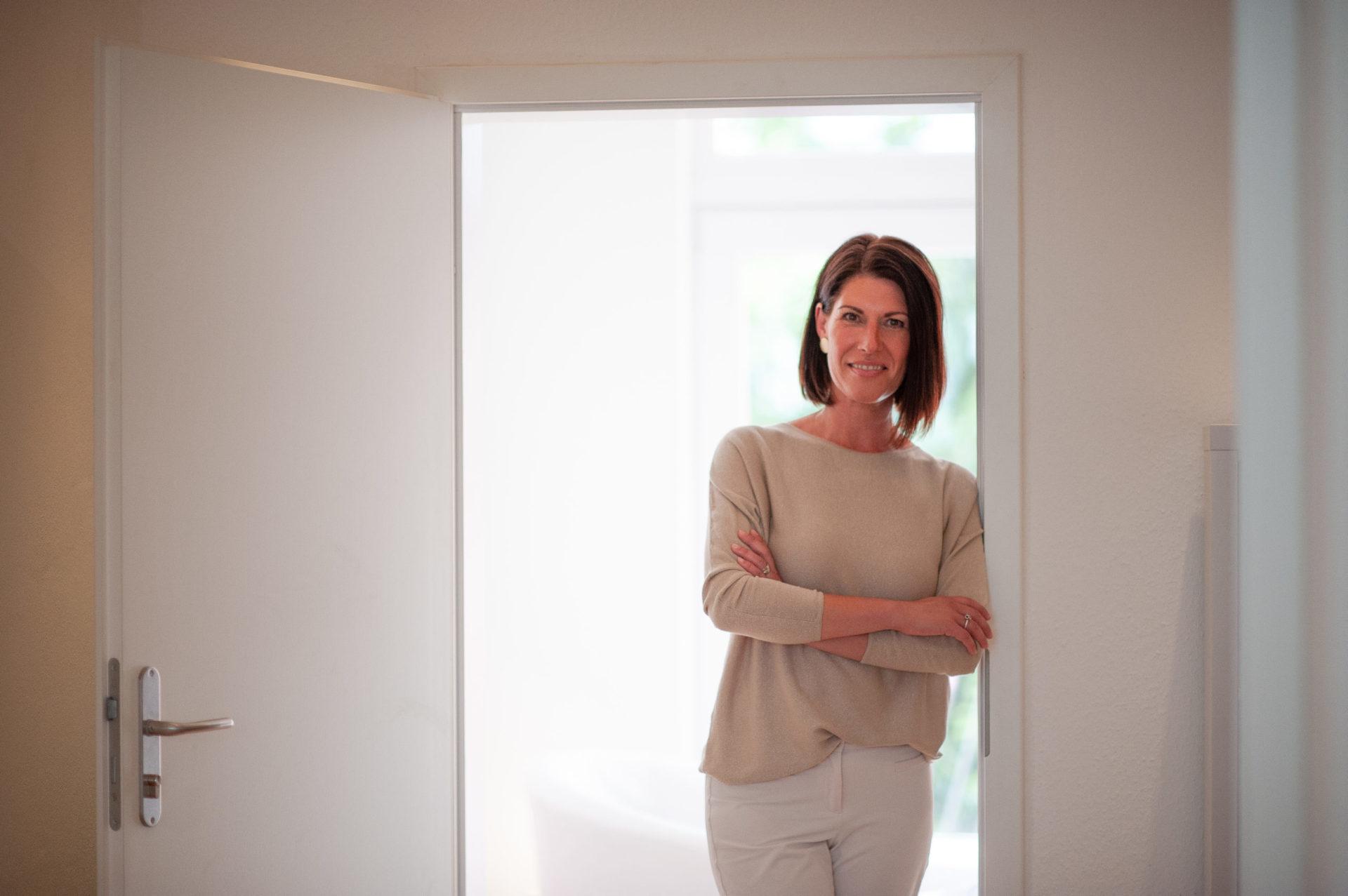 Andrea Lawlor lehnt an Türrahmen in Coachingpraxis