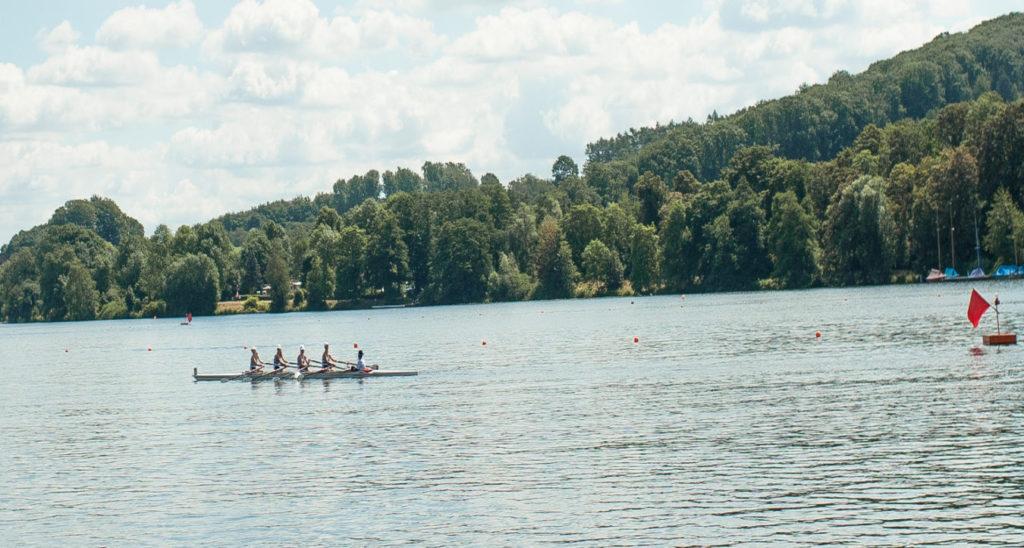 Ein Team aus Ruderern rudert die Regattastrecke auf dem Baldeneysee entlang