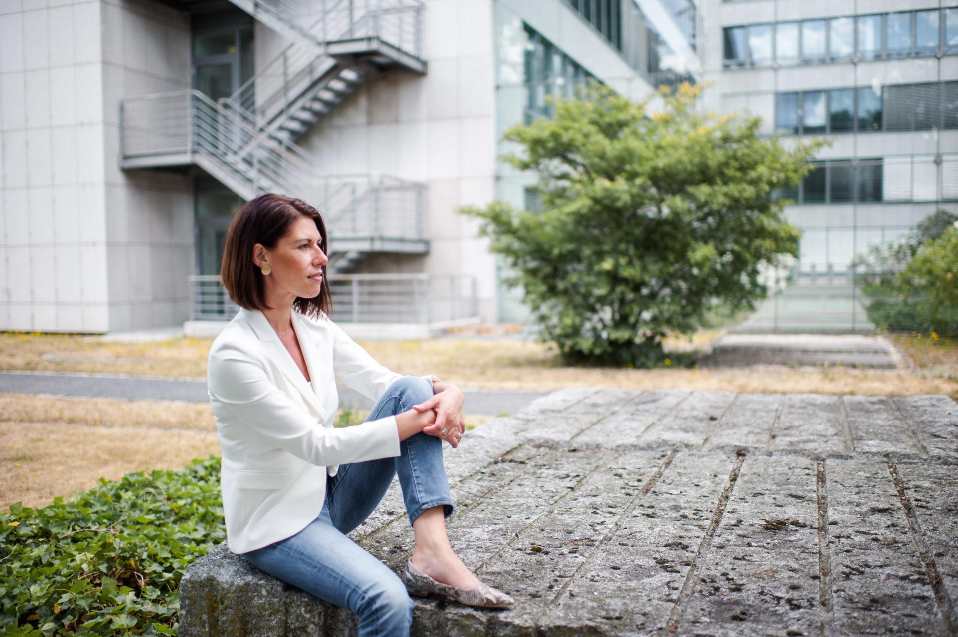 Andrea Lawlor sitzt vor einem Bürogebäude auf einem Stein und blickt in die Ferne