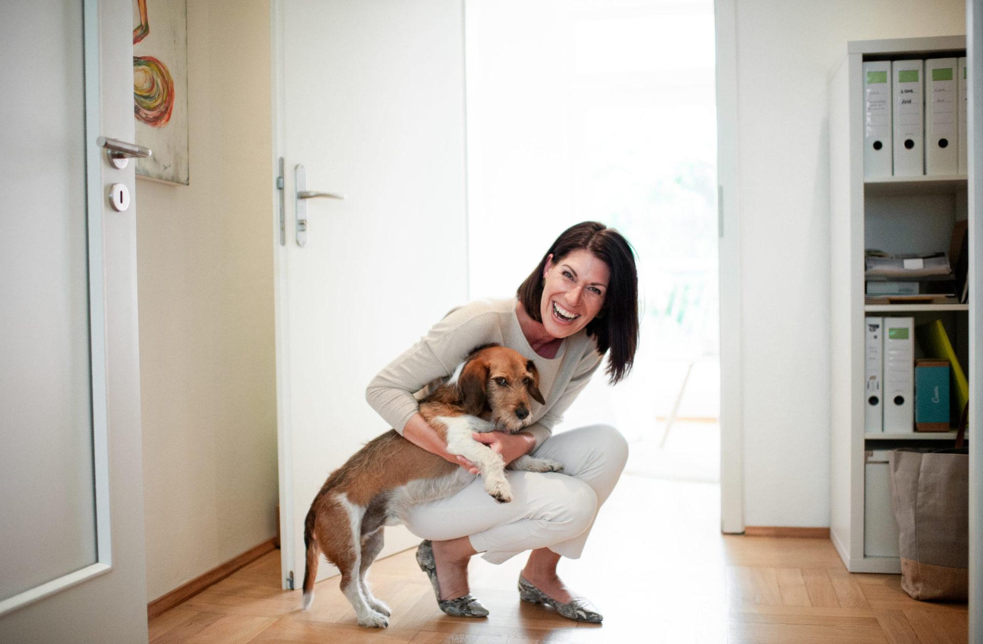 Andrea Lawlor ist hinuntergebeugt und hält ihren Hund Jeff im Arm, der das mit einem grisgrämigen Blick kommentiert