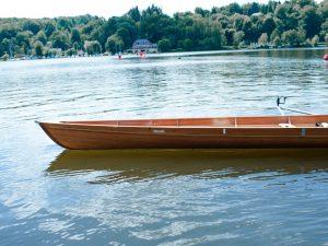 Ein leeres Ruderboot ragt in den Baldeneysee hinein, sein Name ist