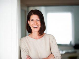 Portrait von Andrea Lawlor, Nahaufnahme davon, wie sie lachend in einen Türrahmen gelehnt steht und mit verschränkten Armen erwartungsvoll blickt