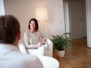 Andrea Lawlor lächelt einen Coaching-Clienten aufmerksam an