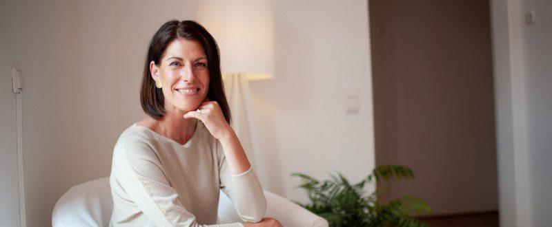 Andrea Lawlor sitzt einem Clienten gegenüber in einem weißen Sessel in ihrer Coaching-Praxis und lauscht offen ihrem Gegenüber